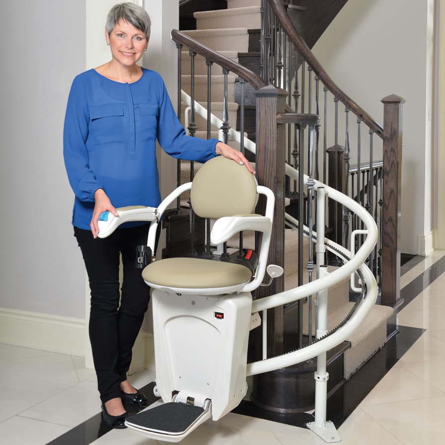 Savaria Stairfriend Stairlift Model Standing Beside Stairlift